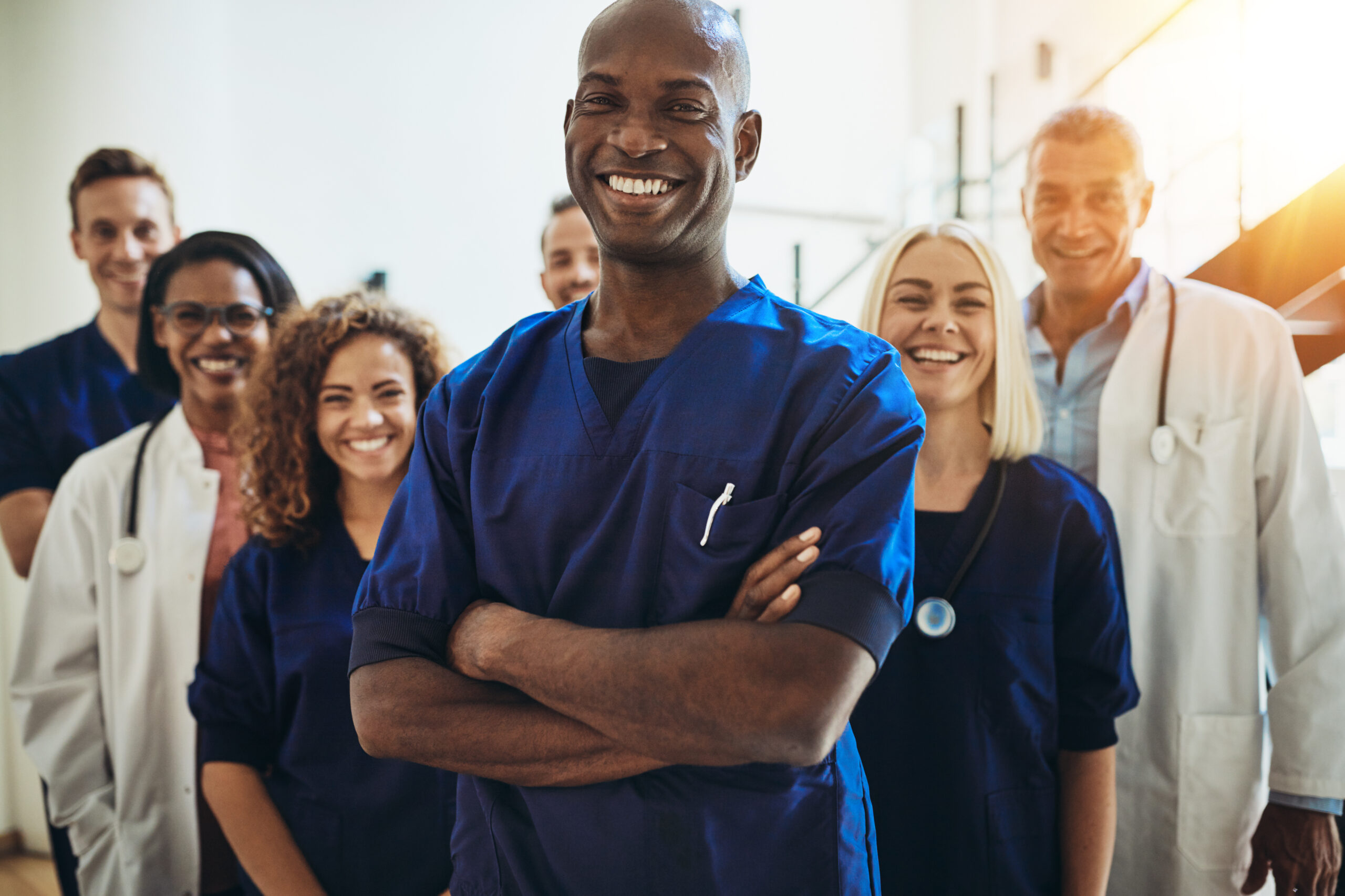 oung African male doctor smiling while standing in a hospital corridor with a diverse group of staff in the background